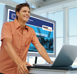 Man smiling standing in front of laptop.