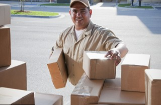Delivery driver removing packages from the back of a vehicle.