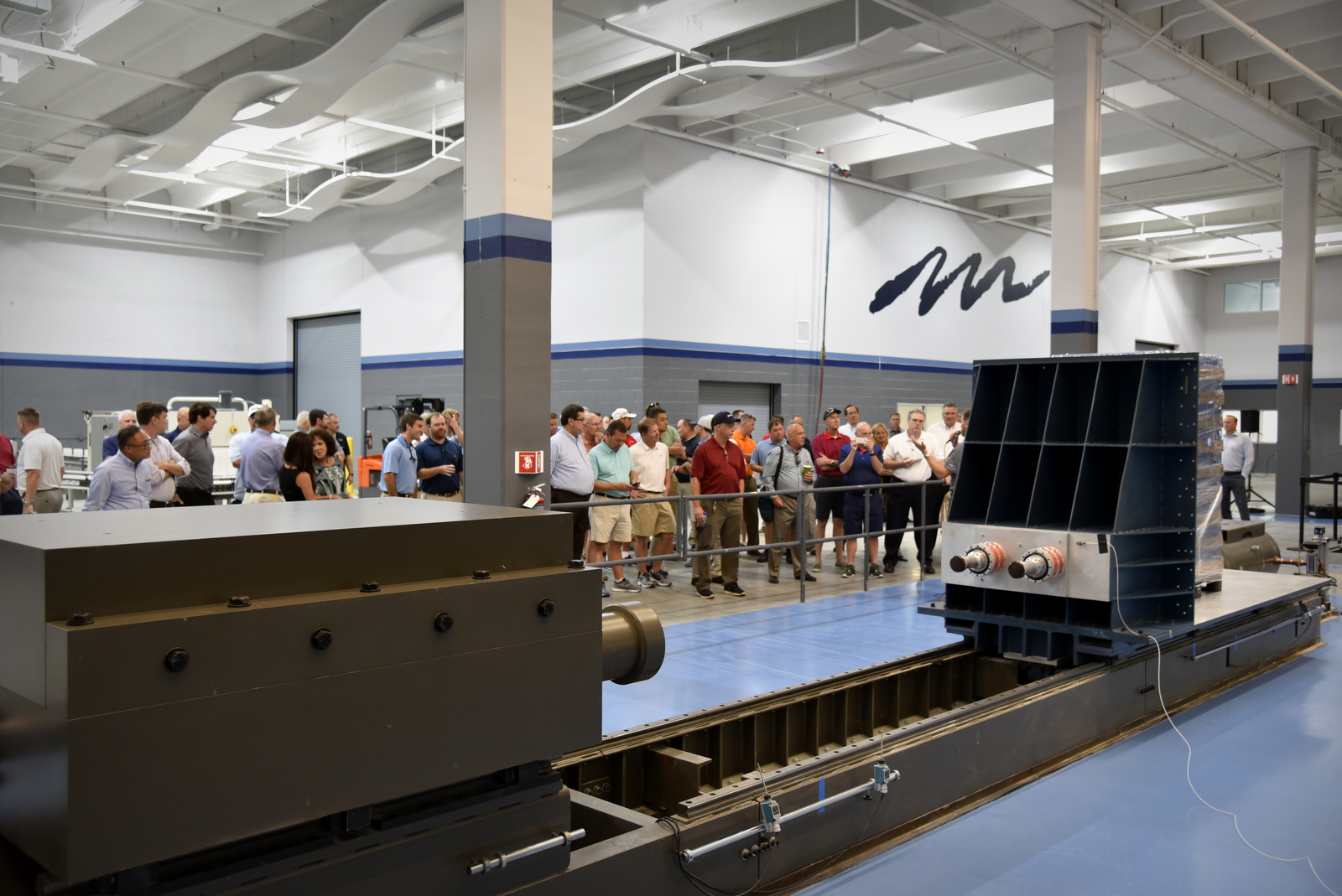 Crowd of people watching a demonstration of Lansmont's horizontal impact test system (HITS).